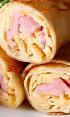 Buckwheat pancakes with ham and semisolid cheese